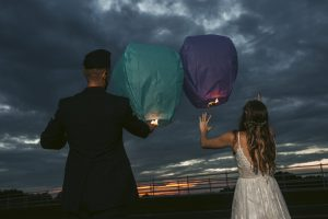 Bride and Groom releasing lanterns outside at sunset
