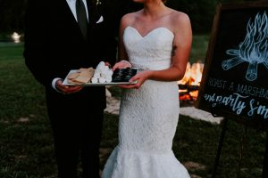 Bride and groom holding smores at outdoor wedding venue